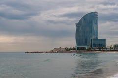 Surfer im Meer mit modernem Hotel auf dem Strand Stockbilder