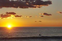 Surfer im Wasser bei dem Sonnenuntergang, der auf die letzte Welle wartet Stockfotografie