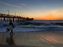 Surfer at Imperial Beach in San Diego, California lit by a stunning sunset Stock Photos