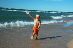 Surfer Jumper Boy. Young boy frolicking surfside Royalty Free Stock Photography