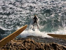 Surfer jumping into the Pacific Ocean Royalty Free Stock Images