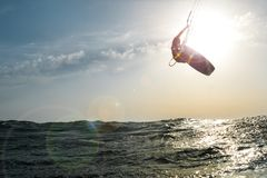 Surfer jumping at sunset over the golden sea. Surfer jumping in front of the sun at sunset over the golden sea, while a beautiful flare enters the camera Royalty Free Stock Photo