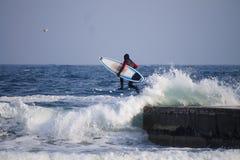 Surfer jumping into water in winter. Surfer jumping into water wearing a wetsuit in winter. Cold surfing. Wave splash. waterproof suit Stock Image