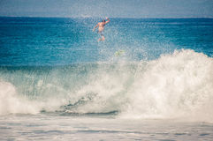 Surfer jumps on board on wave. Indonesia, Bali - December 10, 2013: surfer jumps on board on wave Stock Photo