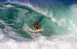 Surfer Kalani Robb Surfing at Backdoor. Photo of pro surfer, Kalani Robb, rides the tube of a wave during the Pipeline Masters surf contest, the third jewel of Royalty Free Stock Photography