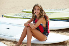 Surfer kid girl sitting in surfboard on the beach Stock Photo