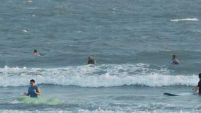 Surfer-Lüge auf den Surfbrettern, die Wellen im Ozean fangen stock footage