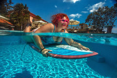 Surfer. Lady lying on the surfboard stock photography