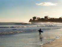 Surfer laissant des vagues au coucher du soleil le jour venteux Photo stock