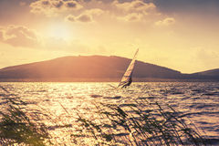 Surfer on lake at sunset. Vintage effect. Beautiful summer landscape Stock Images