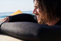 Surfer leaning on surfboard in sea. Close-up of smiling surfer leaning on surfboard in sea Stock Photography