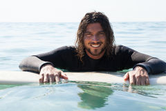 Surfer leaning on surfboard in sea. Portrait of smiling surfer leaning on surfboard in sea Stock Images