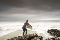 Surfer Leaping in to Ocean Royalty Free Stock Images