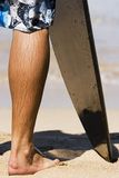 Surfer Leg. Close up shot of a surfer boy's leg on the beach with his board royalty free stock photos