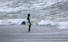 Surfer in Levanto. A girl with the surfboard on beach stock image