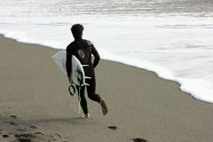 Surfer in Levanto. A boy with the surfboard on beach stock images
