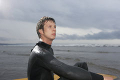 Surfer Looking Away While Sitting In Water At Beach. Young male surfer looking away while sitting in water at beach Stock Photos