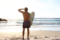 Surfer looking at waves in the sea. Portrait from behind of surfer looking at waves in the sea Royalty Free Stock Photo