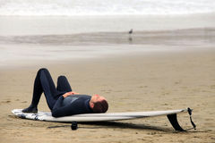 Surfer. Lying on a board resting on the beach Stock Photography