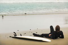 Surfer. Lying on a board resting on the beach Royalty Free Stock Photo