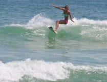Surfer-Mädchen, das eine Welle in den äußeren Banken von NC schnitzt lizenzfreies stockbild