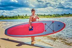 Surfer male with a muscular body with his surfboard at the beach. Shirtless surfer male with a muscular body with his surfboard at the beach Royalty Free Stock Images