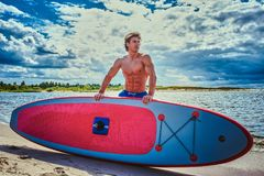 Surfer male with a muscular body with his surfboard at the beach. Shirtless surfer male with a muscular body with his surfboard at the beach Royalty Free Stock Photography