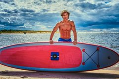 Surfer male with a muscular body with his surfboard at the beach. Shirtless surfer male with a muscular body with his surfboard at the beach Stock Photography