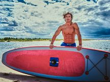 Surfer male with a muscular body with his surfboard at the beach. Shirtless surfer male with a muscular body with his surfboard at the beach Royalty Free Stock Photo