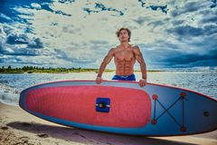 Surfer male with a muscular body with his surfboard at the beach. Shirtless surfer male with a muscular body with his surfboard at the beach Stock Photos