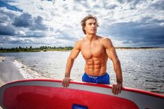Surfer male with a muscular body with his surfboard at the beach. Shirtless surfer male with a muscular body with his surfboard at the beach Stock Photo