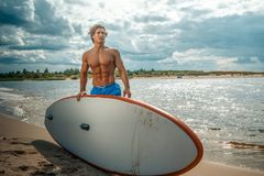 Surfer male with a muscular body with his surfboard at the beach. Shirtless surfer male with a muscular body with his surfboard at the beach Stock Image