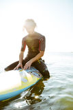 Surfer man in eyeglasses sitting on surf board in ocean Royalty Free Stock Photography