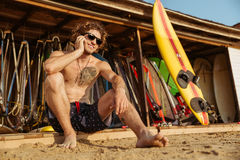 Surfer man in eyeglasses sitting and talking on smartphone outdoors. Young handsome surfer man in eyeglasses sitting and talking on smartphone outdoors Stock Image
