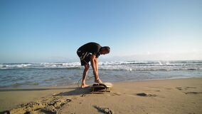 Surfer man fastens leash at leg on the beach.