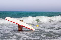 Surfer man holds his surfboard above his head in the waves of the sea stock photo