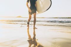 Surfer man with long board walking out fro sea waves on sunny ocean beach. Active vacation spending time concept image stock images