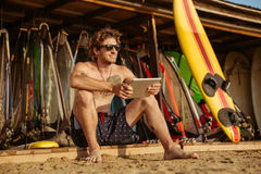 Surfer man with pc tablet. Smiling young surfer man using tablet while sitting on on the beach Royalty Free Stock Photography