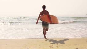 Surfer man run in the ocean.