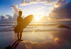 Surfer man standing on beach and holding a surfboard. With sunset background Royalty Free Stock Photo