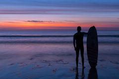 Surfer man standing on the beach holding surfboard at sunset. Silhouette of a surfer on coast in the evening light Royalty Free Stock Images