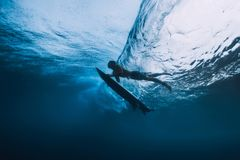 Surfer man with surfboard dive underwater of big ocean wave. stock images