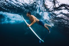 Surfer man with surfboard dive underwater with ocean wave. Surfer with surfboard dive underwater with under sea wave royalty free stock photo