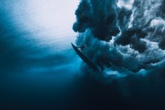 Surfer man with surfboard dive underwater with under big wave. royalty free stock image