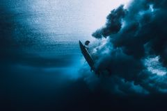 Surfer man with surfboard dive underwater with under ocean wave. stock photo