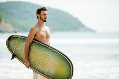 Surfer man with surfboard on sea coast. Royalty Free Stock Photo