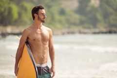 Surfer man with surfboard on sea coast. Royalty Free Stock Image