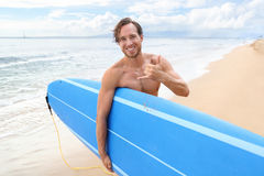 Surfer man surfing doing hawaii shaka surf sign. Surfer guy happy with surf surfing smiling doing hawaiian shaka hand sign for fun during surf session in ocean royalty free stock images