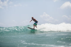 Surfer man surfing on waves splash actively Royalty Free Stock Image