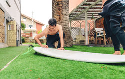 Surfer man with wetsuit waxing woman surfboard. Portrait of surfer men with wetsuit waxing surfboard of a beautiful woman. Summer sports concept Royalty Free Stock Photography